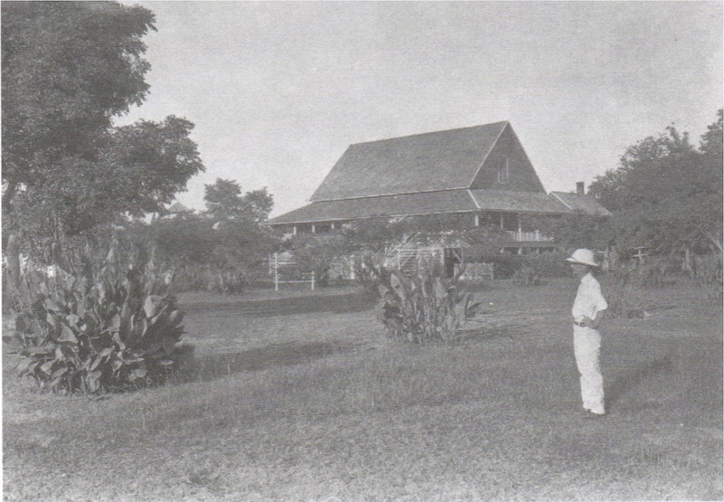 Man standing in a garden with old house