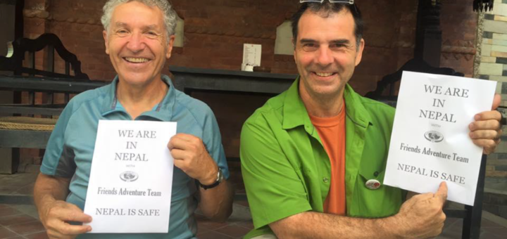 Two foreigners holding a sign We are in Nepal after the earthquake